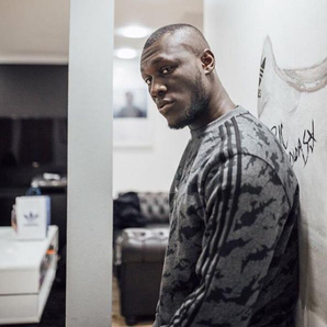 Stormzy leaning against wall